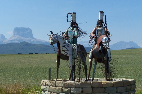North Entrance to the Blackfeet Indian Reservation with Chief Mountain in the background.  Metal warriors by Jay Labor, enrolled member of the Blackfeet Nation